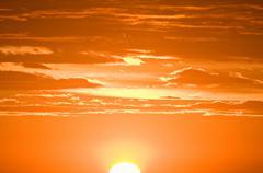 A sun setting against an orange sky Stock Photos
