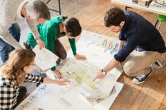 High angle view of architects discussing blueprints on wooden floor Stock Photos