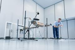 Engineer testing vehicle exhaust system in anechoic chamber Stock Photos
