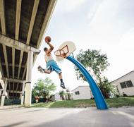 Low angle view of young man in mid air holding basketball jumping for hoop - stock photo