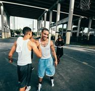 Young men on basketball court connecting with handshake after basketball game - stock photo