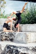Two men practicing advanced yoga on park step Stock Photos