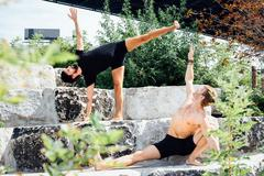 Two men practicing yoga positions together on park step Stock Photos