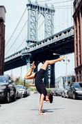 Man practising yoga handstand in front of Manhattan Bridge, New York, USA Stock Photos