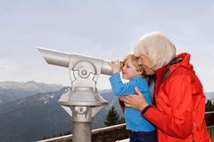 Boy, grandma looking through telescope Stock Photos