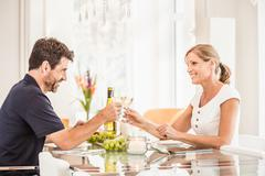 Mature couple sitting at table, holding wine glasses, making toast - stock photo