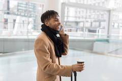 Young businessman talking on smartphone in train station atrium Stock Photos