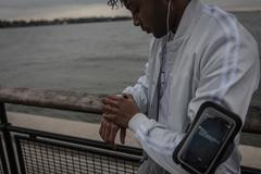 Young man training on riverside at dawn timing on smartwatch Stock Photos