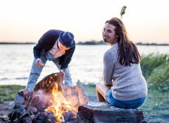Young woman waiting for man preparing campfire by sea - stock photo