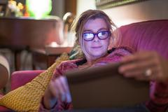 Mature woman wearing eye glasses reclining on sofa using digital tablet Stock Photos