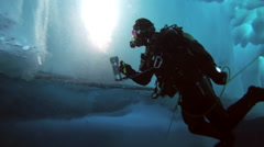 Diver under Arctic ice at the North Pole light the way a flashlight. - stock footage