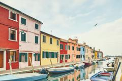 Traditional multi colored houses and moored boats on canal, Burano, Venice, Stock Photos