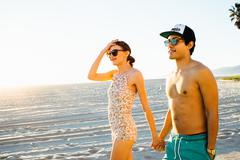 Young couple wearing swimming costume and shorts strolling on beach, Venice Stock Photos