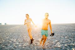 Young couple wearing swimming costume and shorts running on sunlit beach, Venice Stock Photos