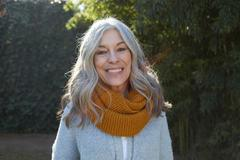 Portrait of woman with long gray hair looking at camera smiling Stock Photos