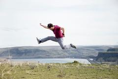 Man jumping, in mid air, on mountain top, Colombia River Gorge, Washington, USA Stock Photos