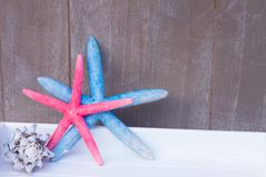 red and blue starfish  on wooden board - stock photo