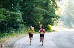 Young woman and teenage girl running along rural road, rear view - stock photo