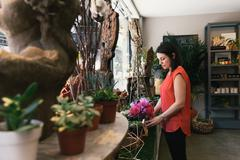Florist arranging display in flower shop - stock photo