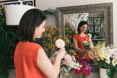 Florist arranging bouquet in flower shop, rear view Stock Photos