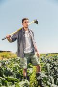 Man in vegetable garden carrying hoe on shoulder looking away Stock Photos