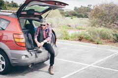 Male hiker sitting on car boot tying hiking boot laces, Crystal Cove State Park, Stock Photos
