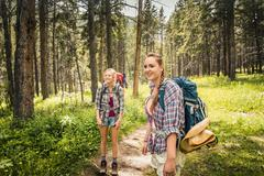 Teenage girl and young female hikers looking back in forest, Red Lodge, Montana, - stock photo