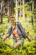 Young female hiker hiking through forest undergrowth, Red Lodge, Montana, USA - stock photo