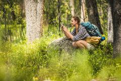 Young female hiker photographing in forest, Red Lodge, Montana, USA - stock photo