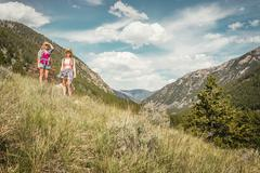 Teenage girl and young female hiker looking out from mountain, Red Lodge, - stock photo