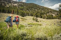 Rear view of teenage girl and young female hiker hiking up mountain, Red Lodge, - stock photo