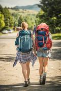 Rear view of teenage girl and young female hiker hiking on rural road, Red - stock photo