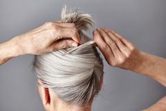 Rear view of woman styling gray hair into bun Stock Photos