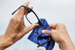 Womans hands cleaning eye glasses with cloth Stock Photos