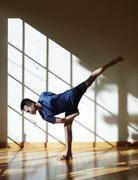 Man doing yoga in studio, in half moon bind position Stock Photos