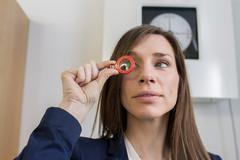 Woman in opticians office looking through optical tool - stock photo