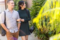 Couple in street, linking arms looking away smiling Stock Photos