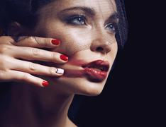 Beauty brunette woman under black veil with red manicure close up Stock Photos