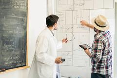 Scientists planning on whiteboard in plant growth research facility laboratory Kuvituskuvat