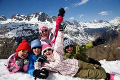 5 kids lying in the snow. Stock Photos
