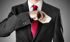 Businessman with red tie puting stack of fifty euro bills into his suit. Stock Photos