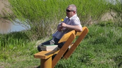 Man with dandelion relax on bench near river - stock footage