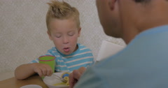 Child having dinner with father at home Stock Footage