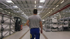 Worker walking though warehouse in factory with camera tracking Stock Footage
