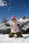 Girl kneeling down throwing snow. - stock photo