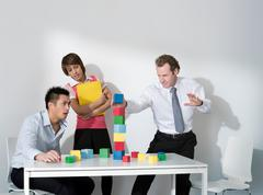 Business man puts last block on tower - stock photo