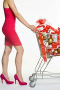 Woman with shopping trolley full of christmas gifts Kuvituskuvat