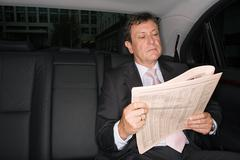Businessman reading a newspaper in car Stock Photos