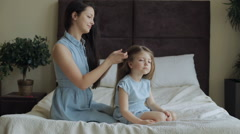 Mother combing daughter hair on bed at home Stock Footage