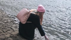 Teen blond girl in pink hat goes up on a stone embankment. Medium shot Stock Footage